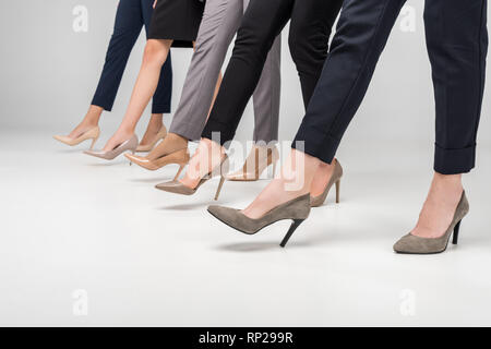 cropped view of businesswomen walking in high heel shoes on grey background - Stock Photo