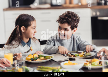 cheerful sister looking at brother while having lunch at home - Stock Photo