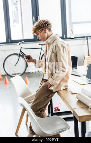 handsome architect using smartphone near table with blueprints in loft office - Stock Photo