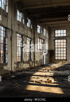Interior of an old abandoned building lightened through the broken windows - Stock Photo