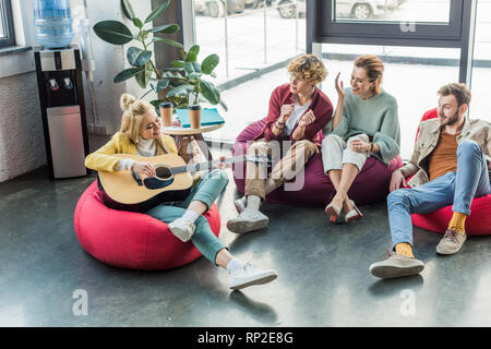 smiling group of friends sitting on bean bag chairs and playing guitar - Stock Photo