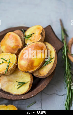 Roasted potatoes with rosemary herb in wooden bowl, tasty freshly baked potatoes - Stock Photo
