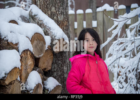 Young Asian girl in pink coat standing next to snow covered log pile - Stock Photo