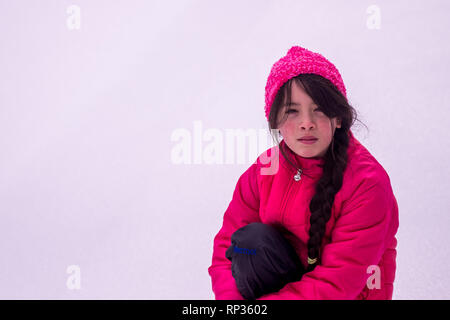 Young Asian girl with pink hat and jacket in snow - Stock Photo