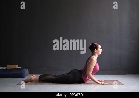 Beautiful sporty fit yogini woman practices yoga asana bhujangasana - Stock Photo