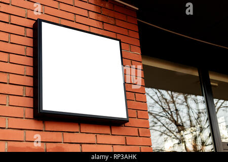 Blank square signboard, business light up sign mock up mounted on the brick wall of a small business workshop store - Stock Photo