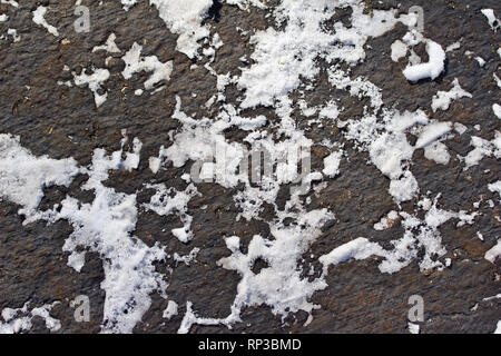 Overhead view macro abstract background of an asphalt road dusted with snow patterns - Stock Photo
