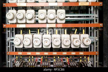 An old fuse box with cables and contactors.  Old electrical panel, electrical box, control panel. Potcelain fuses. - Stock Photo