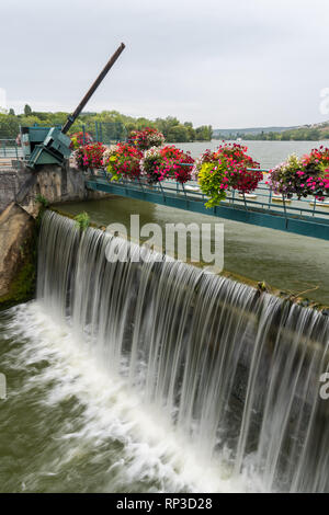 The weir of Kir lake, an artificial lake located south west of Dijon (Burgundy, France) with beautiful flowers on a cloudy day in summer - Stock Photo