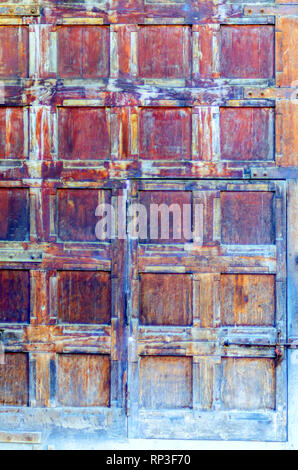 A door in a door! A large wooden door with square blocks, weathered with age and washed out, containing a smaller door with metal hinges and a latch. - Stock Photo