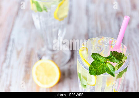 A glass of cool water with ice, lemon and mint. Selective focus. refreshing summer drink. close up. copy space for text. - Stock Photo