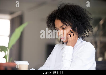 Young serious african office worker female sitting at desk makes business call listens client claim feels displeased and annoyed. Gloomy mixed race em - Stock Photo