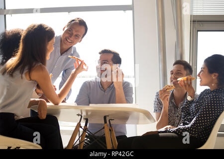 Diverse multiracial workers sitting around the office table holds slices of pizza eating junk food having pleasant conversation with coworkers. Positi - Stock Photo