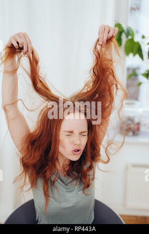 Frustrated young woman having a bad day holding up her long red hair with an agonised expression and closed eyes - Stock Photo