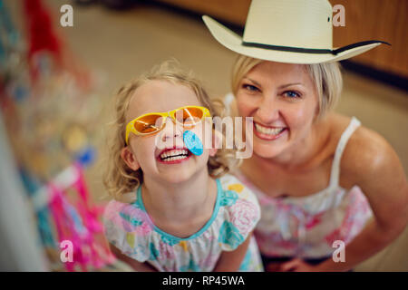 Portrait of a happy young girl and her mother playing dress-up in a beachwear store.