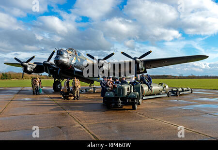 Avro Lancaster bomber Just Jane NX611 with Second World War reenactors loading bombs at East Kirkby, Lincolnshire UK - 16/3/2013 - Stock Photo