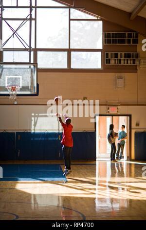 Teenage boy playing basketball - Stock Photo