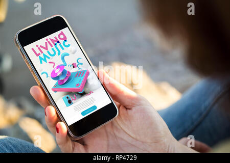 close-up view of young woman browsing music website on her mobile phone. All screen graphics are made up. - Stock Photo