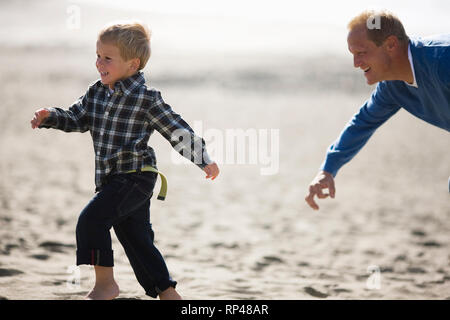 Mid-adult man chasing his young son along a beach. - Stock Photo