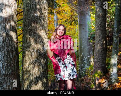 Nature-lover teen girl countrygirl in woodland forest amongst trees wearing red scarf and short skirt mini miniskirt happy smiling - Stock Photo