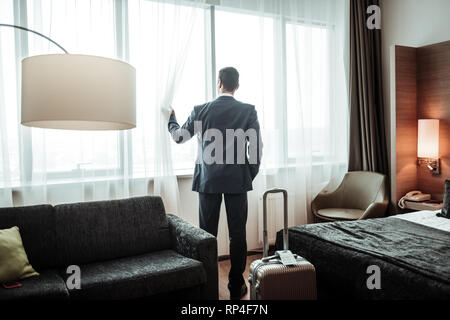 Businessman wearing dark suit looking into window at his hotel - Stock Photo