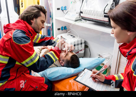 Paramedic doing eye examining in ambulance car - Stock Photo