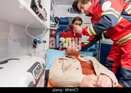 Paramedics doing eye examining in ambulance car - Stock Photo