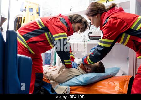 Paramedics in latex gloves doing cardiopulmonary resuscitation - Stock Photo