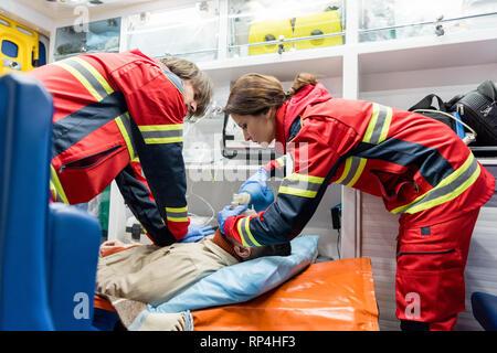 Paramedics doing cardiopulmonary resuscitation in ambulance car - Stock Photo