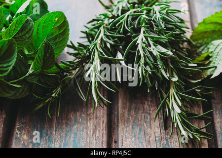 Fresh herbs. Melissa, rosemary and mint in rustic setting. Spices on wood - Stock Photo