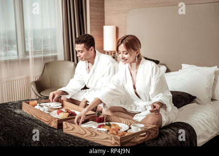 Businessmen feeling relaxed while having breakfast in bed - Stock Photo
