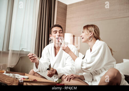 Husband biting piece of little tomato having breakfast with wife - Stock Photo