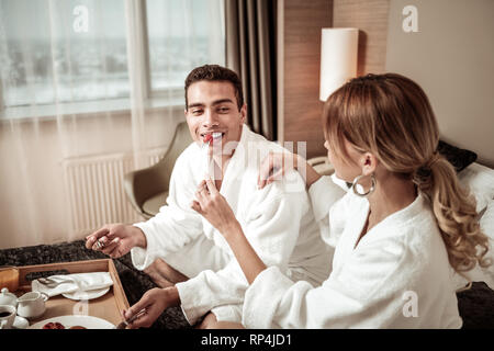 Caring loving wife feeding her husband having breakfast - Stock Photo