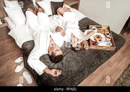 Lovely cute couple chilling on bed after having yummy breakfast - Stock Photo