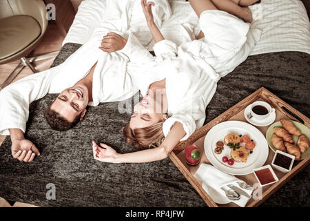 Couple chilling on bed in the hotel before having breakfast - Stock Photo