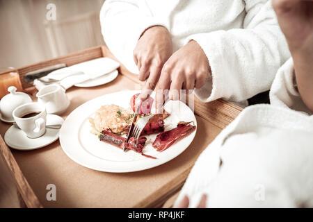 Close up of man wearing bathrobe cutting sausage having breakfast - Stock Photo