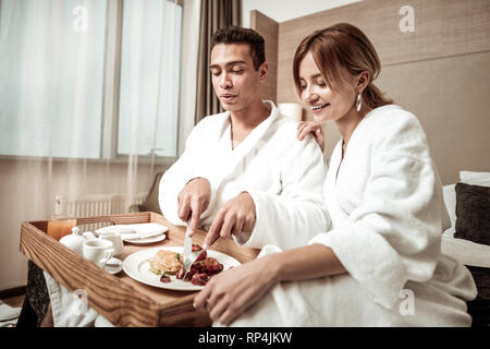 Appealing wife watching her lovely man having delicious breakfast - Stock Photo