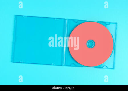 Pastel pink cd in case on pastel blue background. Color of the year 2019 - Living Coral. - Stock Photo