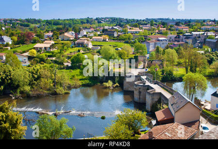 View on an old bridge across Thouet river in a small town of Thouars, France. Many houses among green trees and rooftops. Warm spring morning, vibrant - Stock Photo