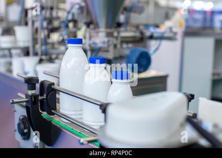 Factory line for bottling milk or yogurt - Stock Photo