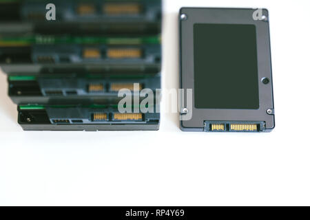 Stack of multiple HDD hard disk drives with modern fast SSD solid state drive placed near them - Stock Photo