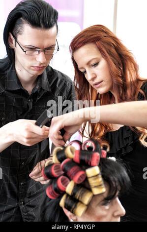 Junge Friseurmeisterin zeigt ihrem maennlichen Auszubildenden wie Lockenwickler gesetzt werden bei einer schwarzhaarigen Kundin. [(c) Dirk A. Friedric - Stock Photo