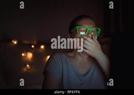 Tired exhausted freelancer woman is working on laptop computer and yawning late at night in her home office - Stock Photo