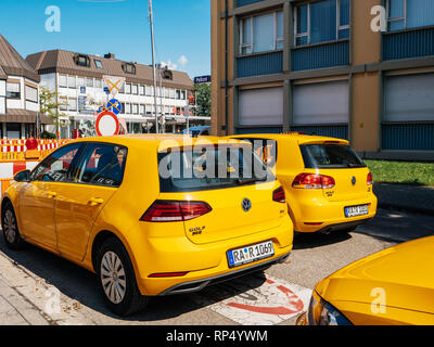 KEHL, GERMANY - SEP 1, 2017: Rear view of fleet of yellow Volkswagen Golf cars parked near construction site in German city - Stock Photo