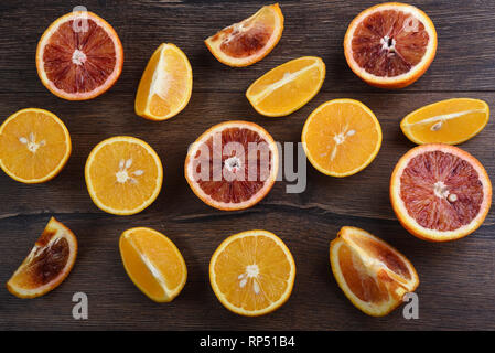 Ripe juicy slices of blood and ordinary oranges on a wooden background. Rustic style - Stock Photo
