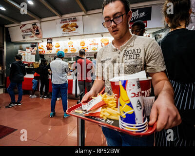PARIS, FRANCE - OCT 13, 2018: Young man with lots of fast-food inside KFC Kentucky Fried Chicken restaurant - Stock Photo
