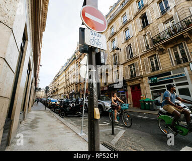 PARIS, FRANCE - OCT 13, 2018: View from the street of people on scooter and bicycles waiting for the green light at the intersection in Paris - Stock Photo