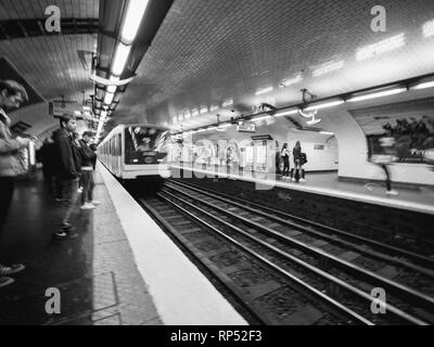 PARIS, FRANCE - OCT 13, 2018: Black and white image of commuters large crowd of people waiting in the Montparnasse bienvenue metro subway station for their train commuting in the metropolitain of paris perspective view - Stock Photo