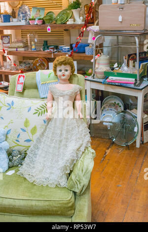 Reddish brown baby doll in formal ballgown waits in an antique store for a new child to love her. - Stock Photo