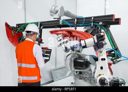 Engineer using laptop computer maintenance robot grip automotive workpiece, Smart factory concept - Stock Photo